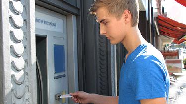 Junge steckt Karte in einen Bankomaten © wildworx, stock.adobe.com
