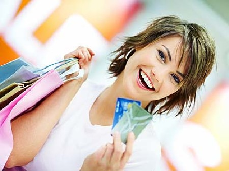 Lächelnde Frau hält mehrere Einkaufstaschen in der einen, zwei Kreditkarten in der anderen Hand. © Yuri Arcurs, Fotolia.com