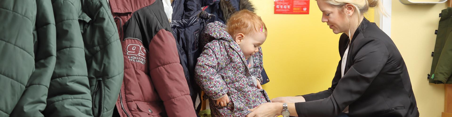 Frau zieht Kleinkind Jacke an © RioPatuca Images, stock.adobe.com