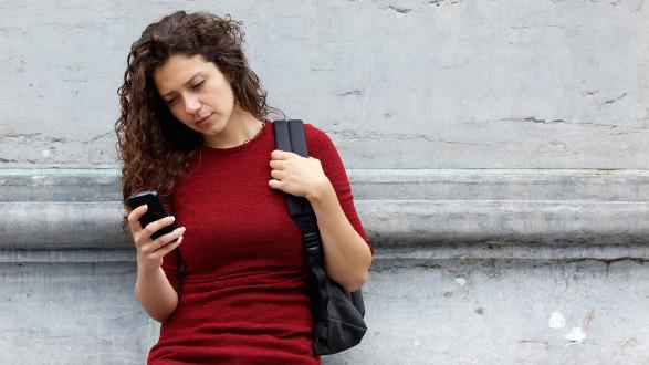 Junge Frau schaut mit ernstem Gesichtsausdruck auf ihr Smartphone © mimagephotos, stock.adobe.com