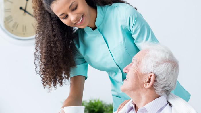 Eine Krankenschwester lächelt einen älteren Patienten an. © Photographee.eu, stock.adobe.com