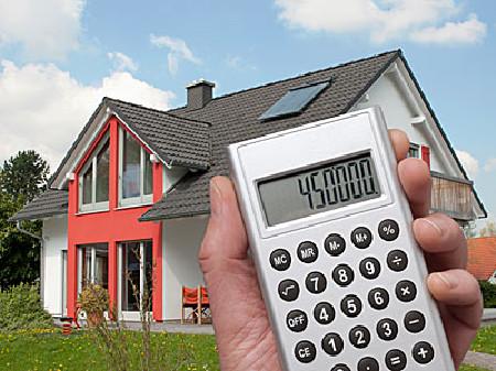 Haus im Hintergrund, Hand mit Taschenrechner im Vordergrund © Eisenhans_Fotolia.com, fotolia.com