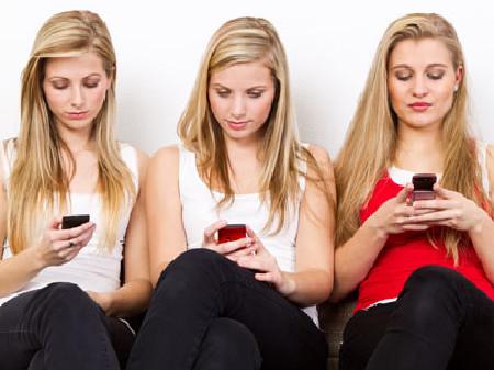 Drei junge Frauen spielen sorglos mit ihren Handys © Picture-Factory, Fotolia.com