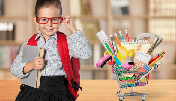 Schülerin mit roter Brille sitzt neben Einkaufswagen voll mit Schulartikel © BillionPhotos.com, stock.adobe.com