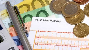 Ein Taschenrechner, ein Kugelschreiber und einige Münzen liegen auf mehreren Euro Banknoten und einem Erlagschein. © RRF, stock.adobe.com