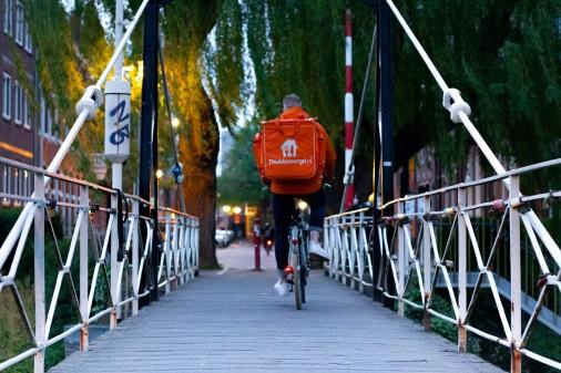 Lieferando Zustellbot*in fährt in der Dämmerung über Brücke, wir sehen die radelnde Person von hinten © Denise Jans Unsplash, Denise Jans Unsplash