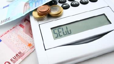 """Auf einem Tisch liegen Geldscheine, Münzen und ein Tischrechner, auf dessen Display """"Sell"""" geschrieben steht © foodinaire, stock.adobe.com"""