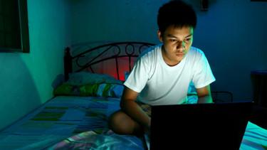 Jugendlicher mit Laptop auf dem Bett © Junpinzon, stock.adobe.com