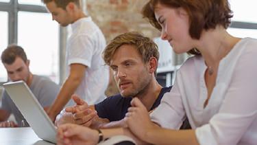 Kollegen diskutieren mit Blick in den Laptop © contrastwerkstatt, Fotolia.com