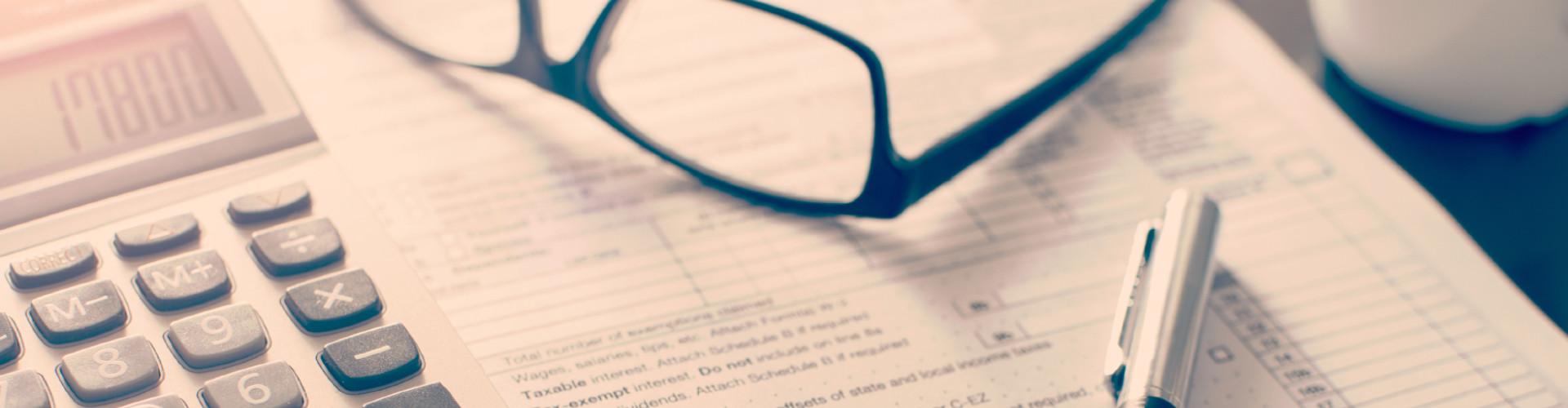 Auf einem Tisch liegen ein Tischrechner, eine Brille und ein Kugelschreiber © devrim_pinar, stock.adobe.com