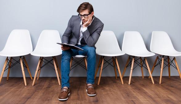 Junger Mann mit Bewerbungsunterlagen in der Hand sitzt in der Mitte einer leeren Sesselreihe und wartet © deagreez, stock.adobe.com