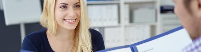 Junge Frau sitzt einem Mann gegenüber, der ihre Bewerbungsmappe liest © contrastwerkstatt, stock.adobe.com